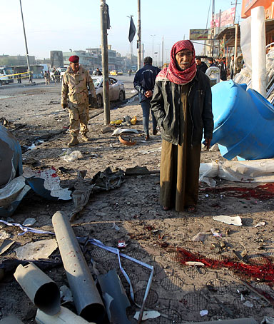An Iraqi man inspects damages at the site of a blast after a bomb ripped through a group of workers in Sadr City in Baghdad on January 24, 2012.
