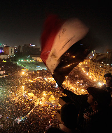 An Egyptian waves the national flag as he and others watch thousands of people gather in Tahrir Square to mark the first anniversary of the popular uprising that unseated President Hosni Mubarak, Cairo, Egypt, Wednesday, Jan. 25, 2012.