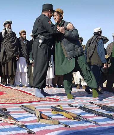 A former Taliban militant, right, hugs with a police official during a joining ceremony with the Afghan government in Baghlan, north of Kabul, Afghanistan, Saturday, Jan. 28, 2012.