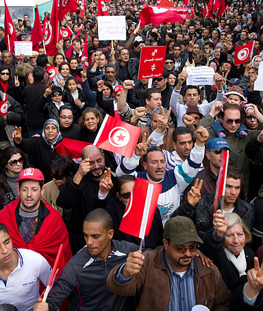 Tunisians shout slogans and wave the national flag during a demonstration organized by leftist opposition parties in Tunis, Tunisia, Saturday, Jan. 28, 2012.