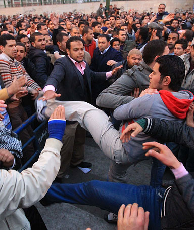 Egyptian anti-government protesters (R) clash with members of the Muslim Brotherhood group (L) as they prevent them from reaching the parliament in Cairo on January 31, 2012