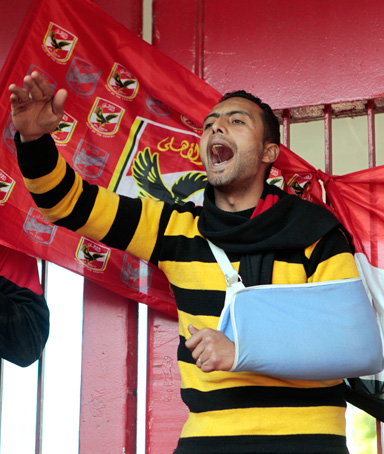 An injured man chants anti-military slogans in front of the Al-Ahly club in Cairo, Egypt, Thursday, Feb. 2, 2012