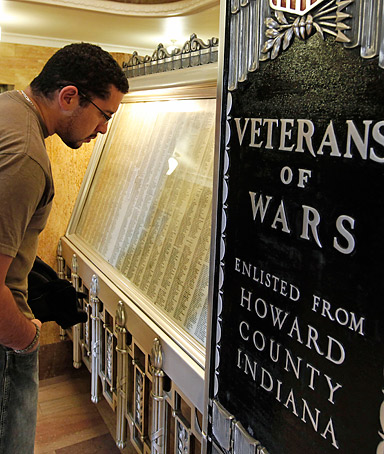In this Thursday, Dec. 8, 2011 photo, Jason Vazquez reads names on a war memorial of those who served and were killed in the line of duty from Howard County at the Howard County Courthouse in Kokomo, Ind.