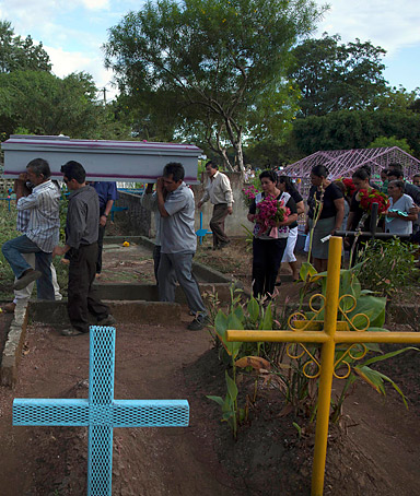 In this Friday, Jan. 20, 2012 photo, relatives and friends of Jesus Ignasio Flores carry his coffin in the cemetery for burial in Chichigalpa, Nicaragua.