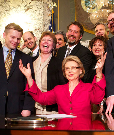 Washington State Governor Chris Gregoire, center, celebrates, with State Rep. Jaime Petersen, far left, State Senator, far right, after signing marriage equality legislation into law February 13, 2012 at the state capitol in Olympia, Washington.