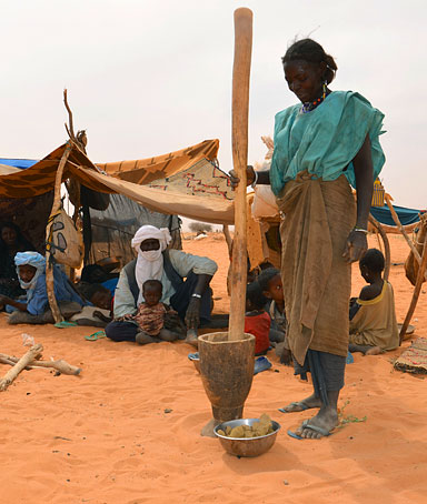 A woman prepares a meal on February 4, 2012 at a Malian refugees camp in Chinegodar, western Niger, close to the Malian border