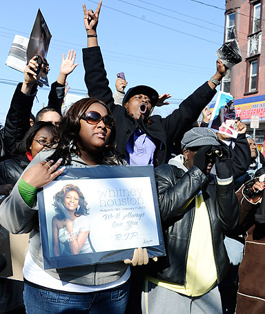 Fans sing near the funeral service for singer Whitney Houston at the New Hope Baptist Church in Newark, N.J., Saturday, Feb. 18, 2012.