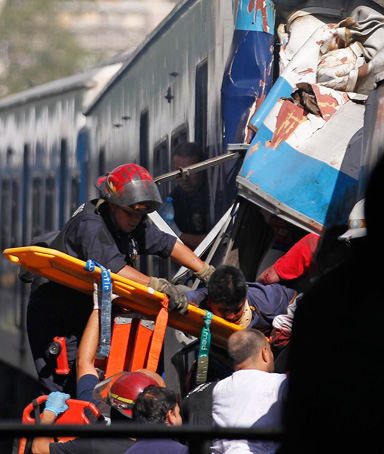 Rescue workers extract a passenger from a commuter train that crashed into the Once train station at rush hour in Buenos Aires February 22, 2012