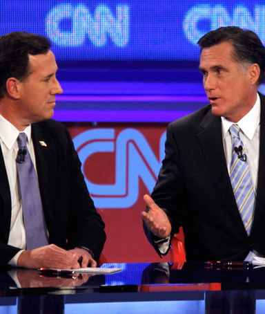 U.S. Republican presidential candidate former U.S. Senator Rick Santorum and former Massachusetts Governor Mitt Romney (right) discuss an issue during the Republican presidential candidates debate in Mesa, Arizona, February 22, 2012