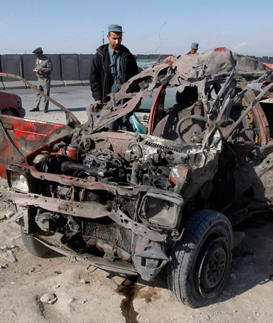 An Afghan policeman inspects a wreckage of a car hit by a car bomb attack in Jalalabad province February 27, 2012