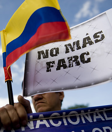 A man holds a Colombian national flag and a banner that reads