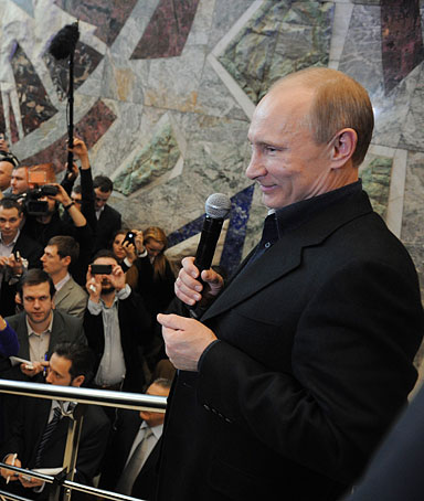 Russia's Prime Minister and presidential candidate Vladimir Putin (top R) smiles as visits his campaign staff in Moscow, late on March 4, 2012