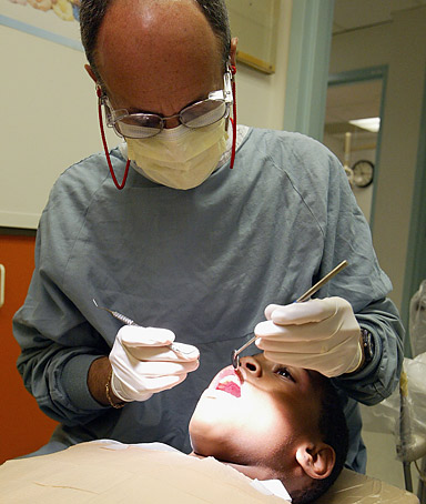 Dentist Edward Rothman performs a dental examination at the pediatric dental clinic of Children's Hospital Oakland on July 9, 2003 in Oakland, California.