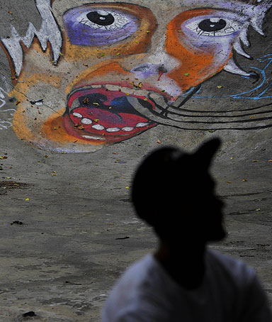 A Russian teenager sits in front of a wall covered in graffiti and street art in Moscow on July 29, 2010