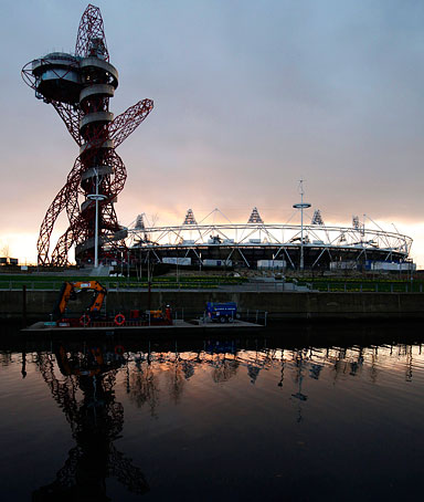 The Olympic stadium and Anish Kapoor's ArcelorMittal Orbit tower are reflected in a canal in Stratford, east London, March 6, 2012