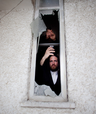 An Israeli man looks out of a window after a rocket attack from the nearby Gaza Strip, on March 12, 2012 in Ashdod, Israel