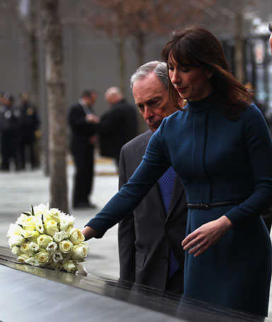 Samantha Cameron lays flowers at the World Trade Center Memorial as her husband British Prime Minister David Cameron (R) and New York Mayor Michael Bloomberg (L), look on March 15, 2012 in New York, New York.