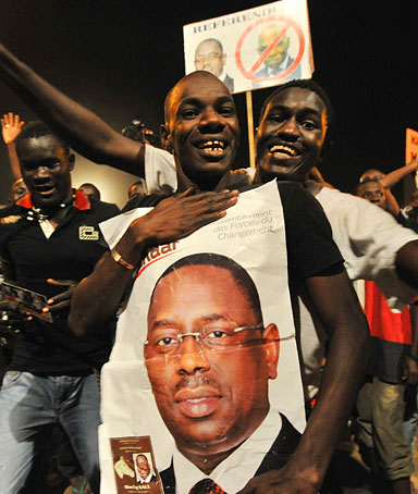 Opposition challenger Macky Sall supporters celebrates their candidate victory at the their campaign headquarter in Dakar March 25, 2012