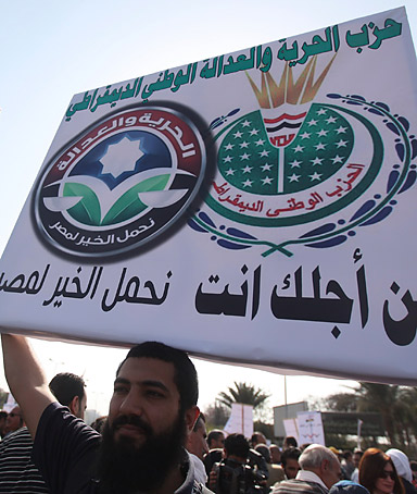 A protester holds up a placard displaying the logos of Muslim Brotherhood's Freedom and Justice party and ousted president Hosni Mubarak's defunct National Democratic Party during a rally outside the Cairo convention centre on March 24, 2012.