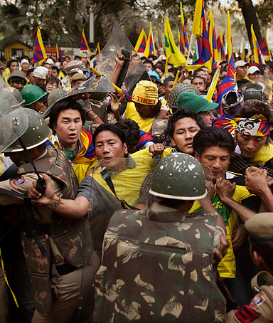 Tibetan protesters scuffle with Indian riot police before being detained during a demonstration against China in New Delhi, India, Monday, March 26, 2012.