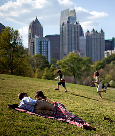 In this March 25, 2012, file photo a couple enjoy a sunny afternoon against the backdrop of the Midtown skyline from Piedmont Park in Atlanta.