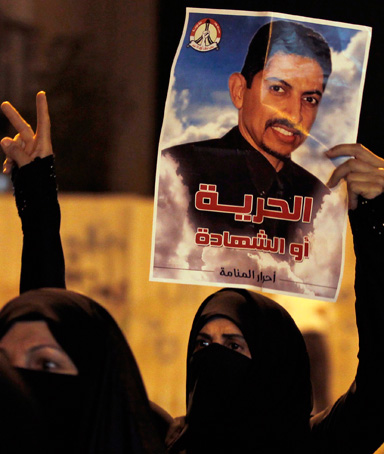 A protester holds a poster of Human Rights Activists Abdulhadi al-Khawaja during an anti-government rally and in support of him, in Manama April 8, 2012