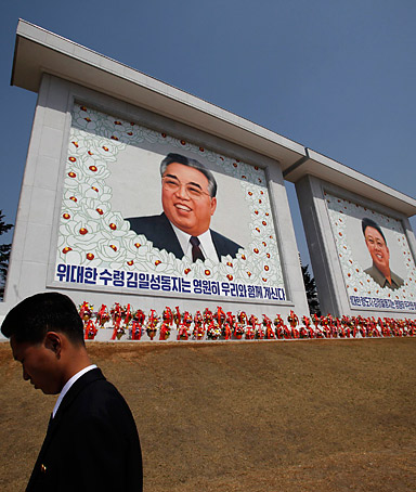 A security guard stands in front of the mosaic portrait of founder of North Korea Kim Il-sung (L) and the new portrait the late leader Kim Jong-il during an inauguration ceremony in Pyongyang April 9, 2012.