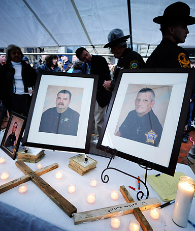 Framed photos of Buchanan County Deputy Sheriff's Eric Rasnake, Shane Charles, Neil Justus and William Stiltner, from left, are displayed on a table at a candlelight vigil Monday, March 14, 2011 outside the county courthouse in Grundy, Va.