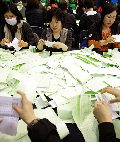 Officials from the South Korean Central Election Management Committee count votes at the Yuido High School on April 11, 2012 in Seoul, South Korea.