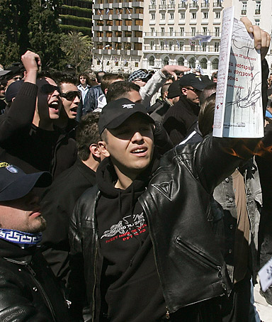 Members of the 'Golden Dawn' nationalist group hold a copy of the Greek sixth-grade history book before burning it, while protesting in Athens during the celebrations of the Greek Independence Day 25 March 2007.