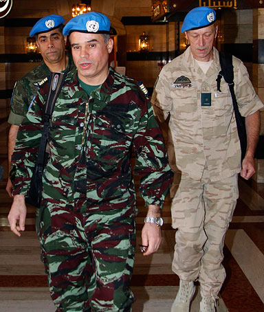 Moroccan Colonel Ahmed Himmiche (front) and two other members of a UN monitors team walk through the lobby of a hotel in Damascus on April 16,2012