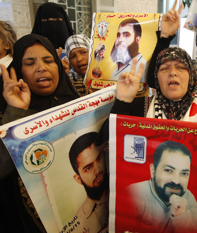 Palestinian women hold up portrait of incarcerated relatives during a protest calling for the release of Palestinian prisoners held in Israeli jails inside the grounds of the Red Cross office in Gaza City on April 16, 2012
