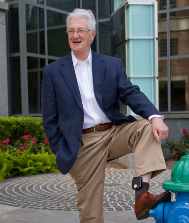 British millionaire Christopher Tappin shows his ankle monitor as he poses outside the offices of his lawyer Dan Cogdell in Houston April 26, 2012