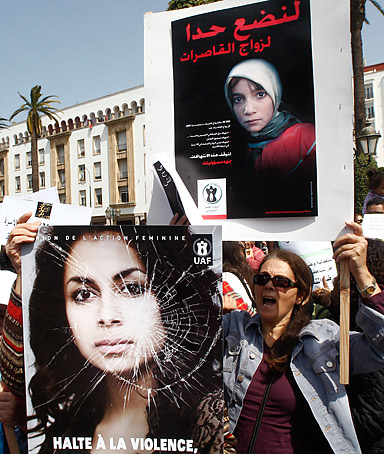 Women hold posters of victims as they protest in support of Amina Filali who committed suicide last week, in front ofthe Moroccan parliament in Rabat, Morocco, Saturday, March 17, 2012.