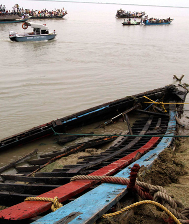 Onlookers and rescue workers look at the damaged boat which was taken on shore after it sank on the Brahmaputra river, at Buraburi village in Dhubri district of the northeastern Indian state of Assam May 1, 2012