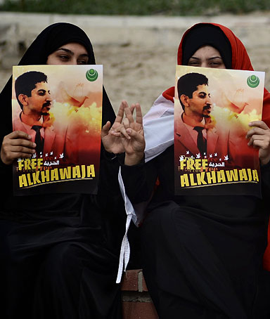 Bahraini Shiite demonstrators hold posters of jailed activist Abdulhadi al-Khawaja during a protest calling for his release in the village of Jidhafs, west of Manama, on April 6, 2012