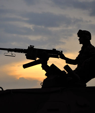 A Colombian soldiers sits atop an armoured personnel carrier (APC), in position along a road in Miranda, Cauca department, Colombia, on March 28, 2011
