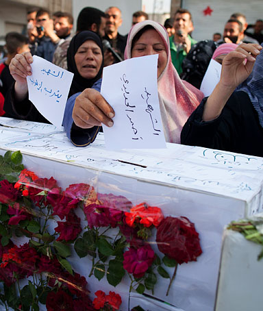 Syrian women cast papers bearing the names of 'martyrs' in coffin-like symbolic ballot boxes during an anti-elections demonstration in the city Qusayr, 15 kms (nine miles) from Homs in restive central Syria, on May 7, 2012