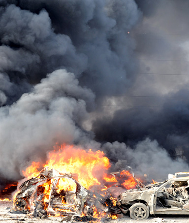 A handout picture from the Syrian Arab News Agency (SANA) shows smoke rising from burning cars at the site of twin blasts in Damascus on May 10, 2012