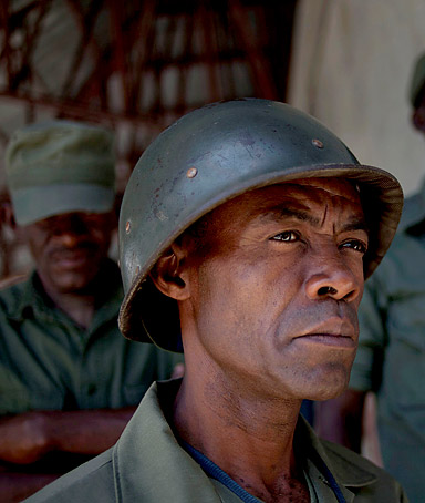 Members of the dissolved Haitian army and civilian volunteers listen to a military  veteran in Port-au-prince.