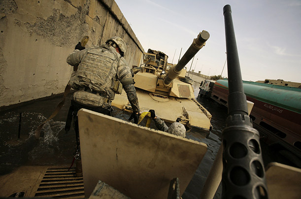 U.S. Army soldiers use a tank to pull a humvee from a flooded intersection in Mosul, Iraq.