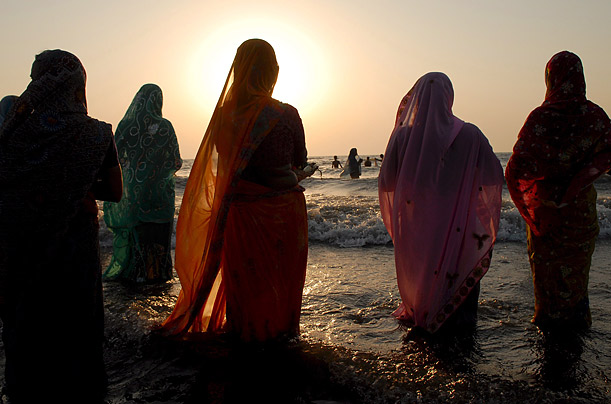 Indian Hindu devotees step into the Arabian Sea with offerings to worship the setting Sun while celebrating Chhat Pooja in Mumbai, India.