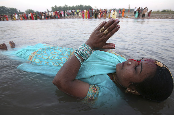 A Hindu woman worships the Sun god in in the Ghaghar River during a Chhat Puja festival in Panchkula, India.