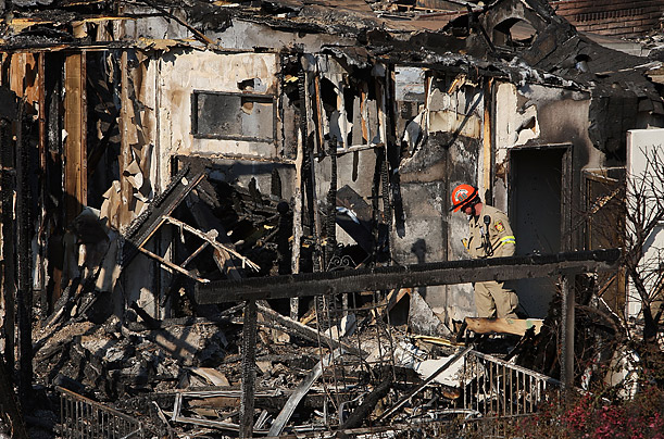 A fireman looks for signs of fatalities in the Oakridge Mobile Home Park in Sylmar, California. 480 homes were destroyed in the park by raging wildfires.