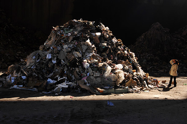 A woman looks at a pile of garbage in France, where 41 tons of waste is produced each minute.