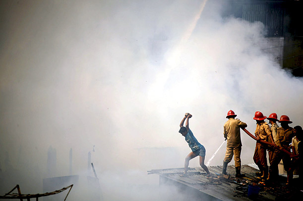 Civilians and firefighters try to extinguish a fire in Dhaka, Bangladesh.