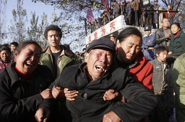 Family members mourn the sole victim in the flooding of a Shaanxian county coal mine in central China's Henan province. Thirty-three other miners were pulled to safety.
