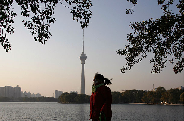 A woman walks in Beijing's Yuyuantan Park. Temperatures in the Chinese capital have dropped suddenly over the last few days.