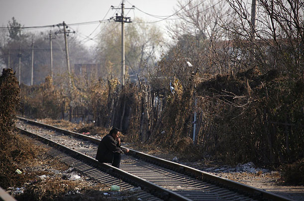 A Chinese man sits on train tracks on the outskirts of Beijing