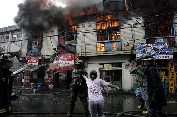 A Filipino resident cries for help as firefighters put out a fire that hit a residential-commercial area in Quiapo, Manila, Philippines.